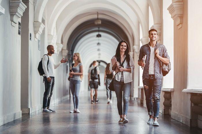 Junge Leute laufen im Gang einer Uni