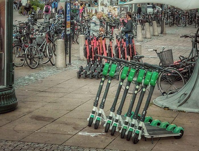 Viele E-Scooter stehen auf einem Platz in einer Stadt