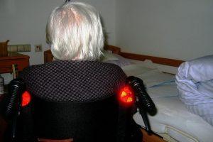 Frau sitzt einsam im Rollstuhl vor dem Bett
