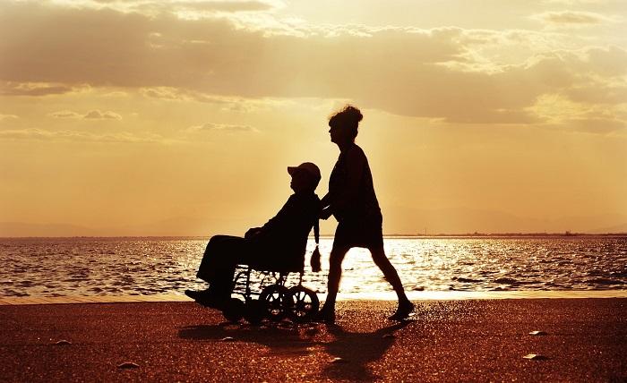 Rollstuhlfahrerin wird an einem Strand spazieren gefahren