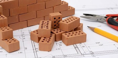 Ziegelsteine liegen auf einem Bauplan