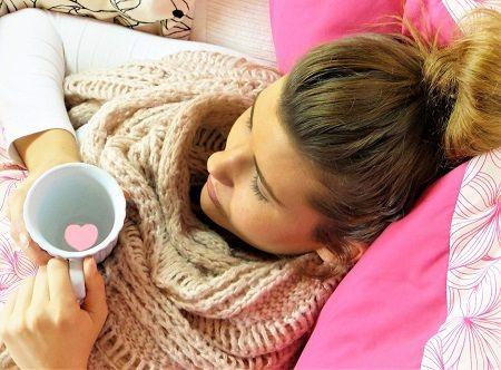 Frau liegt mit einem Becher Tee auf dem Sofa