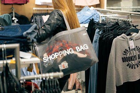 Frau kauft mit einer shopping bag ein