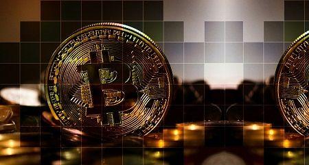 Ein Bitcoin steht zwischen einigen Münzen