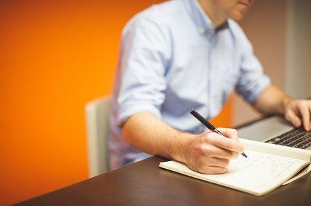 Mann schreibt Notizen auf einen Block