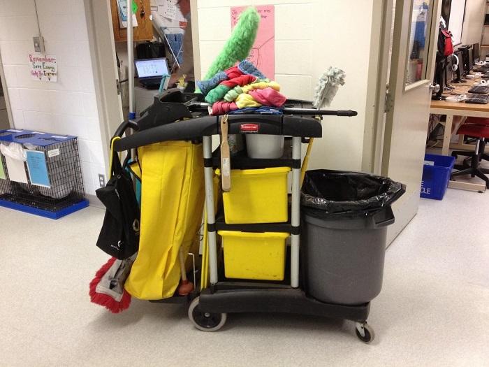 Beladener Putzwagen steht vor Büroräumen