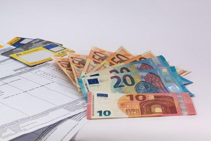 Geldscheine und Kreditkarten liegen auf einer Rechnung
