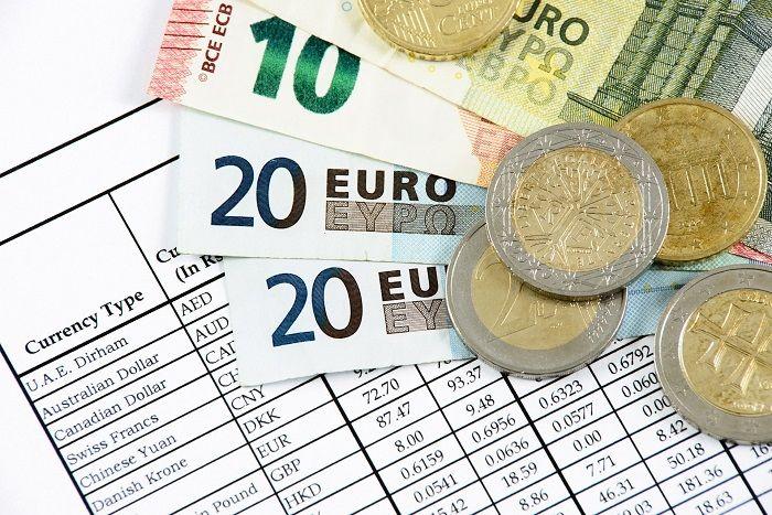 Scheine und Münzen liegen auf einer Währungstabelle