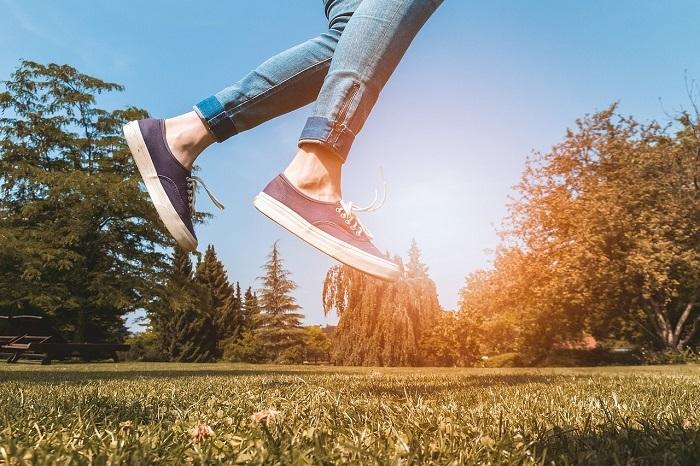 Frau springt im Park hoch, man sieht Ihre bequemen Schuhe