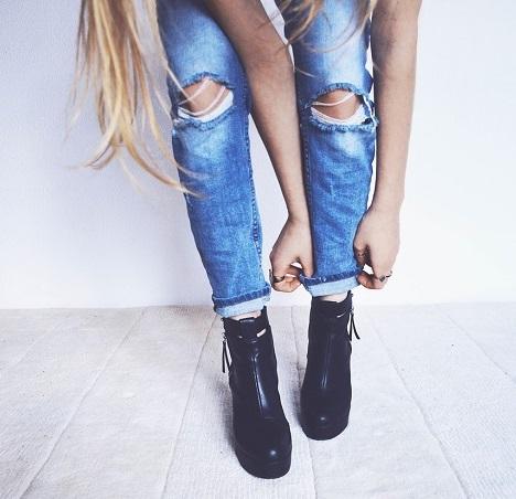 Schwarze Schuhe mit einer modernen Jeans. Frau krempelt sich gerade die Hose hoch.