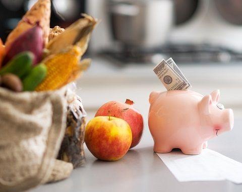 Sparschwein mit einem Geldschein, steht vor einer Einkaufstüte mit Gemüse