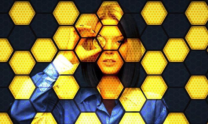 Frau schaut mit einem Bitcoin durch ein Wabenfeld