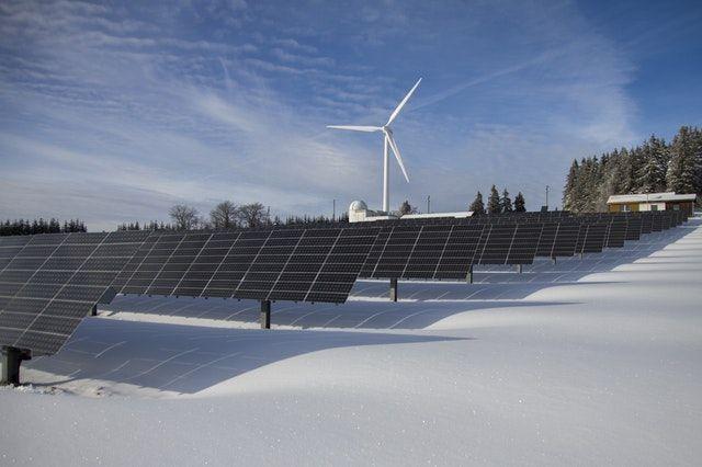 Solarelemente und ein Windrad auf freier Wiesenfläache