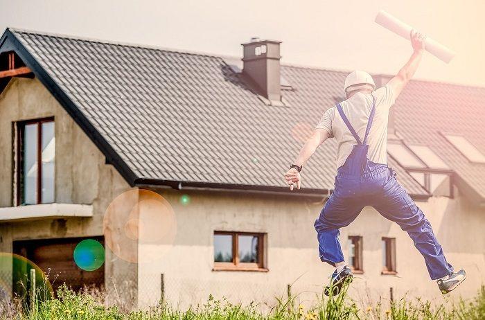 Mann springt vor einem renovierungsbedürftigem Haus, mit einem Plan, freudig in die Luft