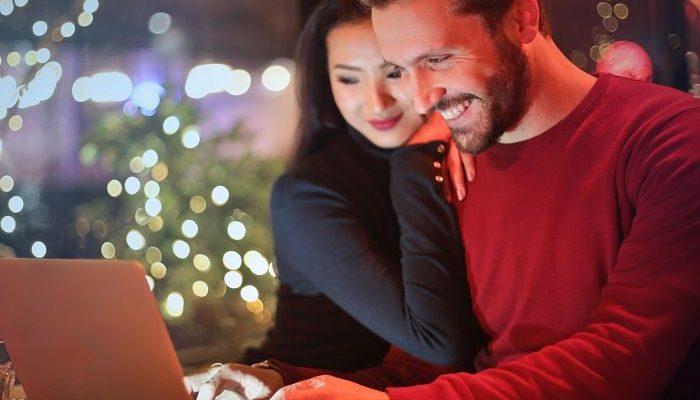 Ein Paar sitzt in der Weihnachtszeit vor dem Laptop