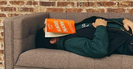 Mann schläft auf der Couch mit einem Buch auf dem Gesicht