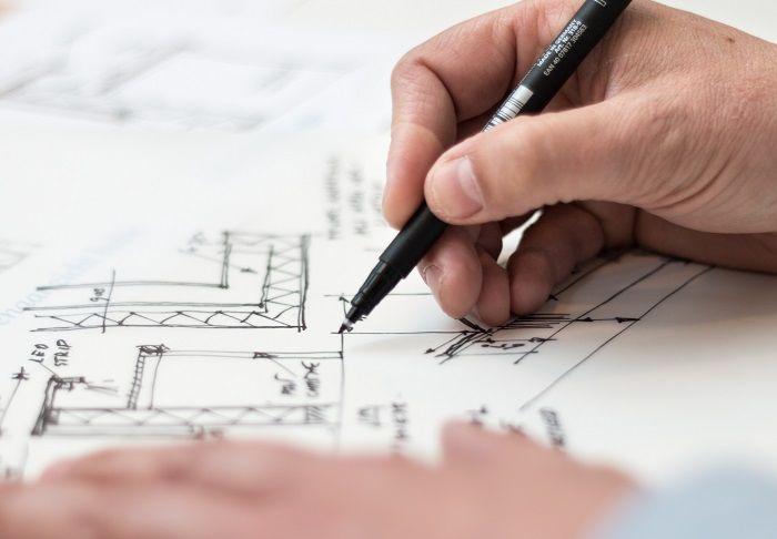 Mann zeichnet an einem Hausplan