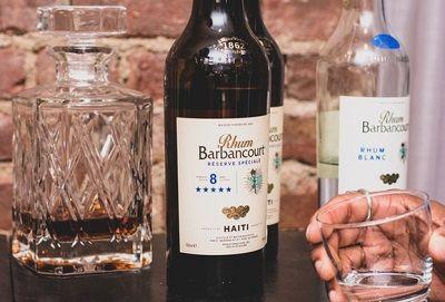 Verschiedene Rumflaschen, davor eine Hand, die ein leeres Glas hält