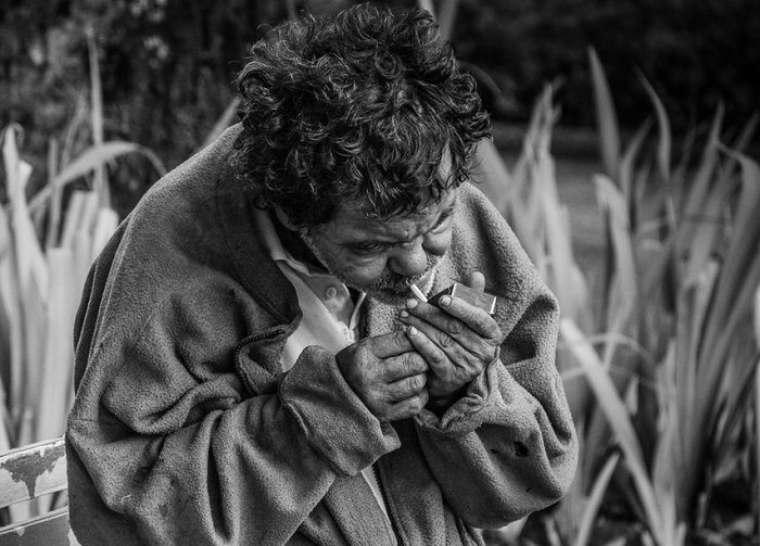 Ein Obdachloser sitzt auf einer Bank und raucht eine Zigarette