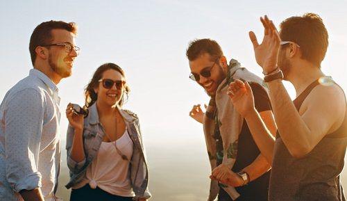 Drei Männer und eine Frau tanzen im Freien