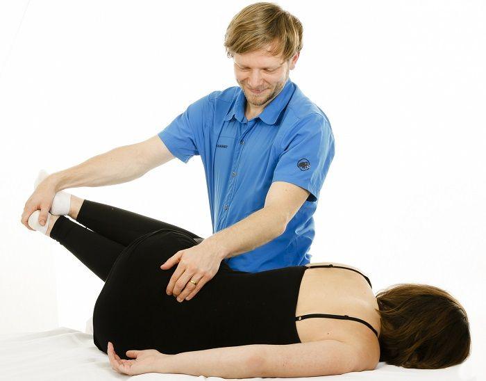 Osteopath behandelt eine Frau im unteren Rücken, der Hüfte und den Beinen