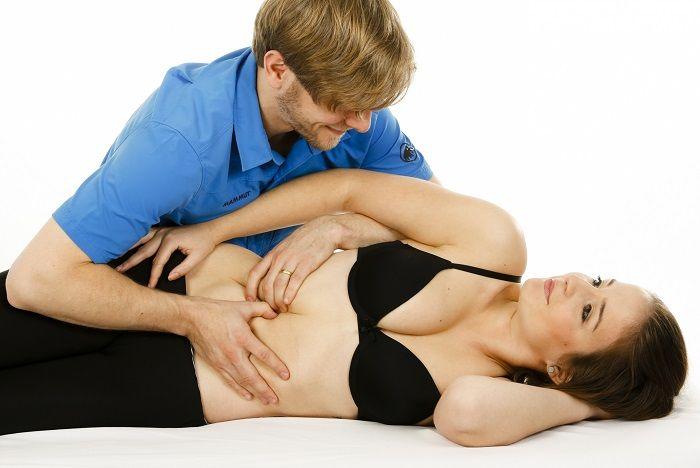 Osteopath behandelt eine junge Frau in Seitenlage