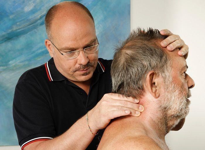 Ein Therapeut behandelt einen Patienten im Halswirbelbereich