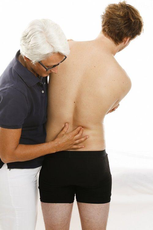 Osteopathien behandelt einen Mann am rücken im Lendenwirbel Bereich