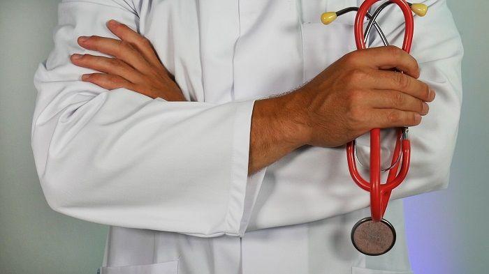 Mann im Arztkittel hält ein Stethoskop in der Hand
