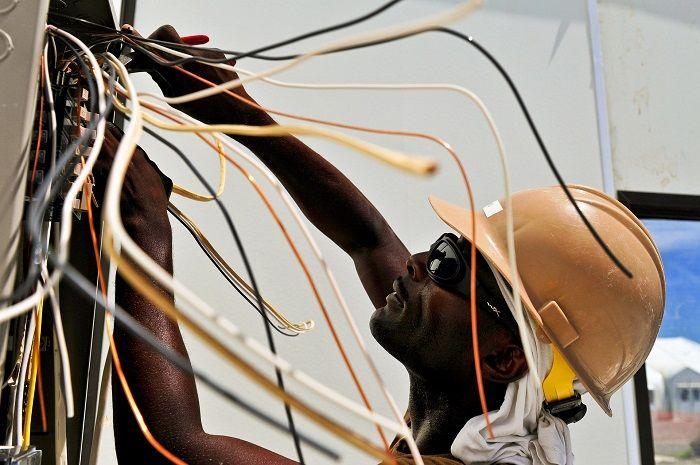 Mann repariert eine Maschine mit vielen bunten Kabeln