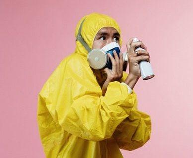 Mann in Schutzanzug und mit Mundmaske sprüht mit Desinfektionsspray