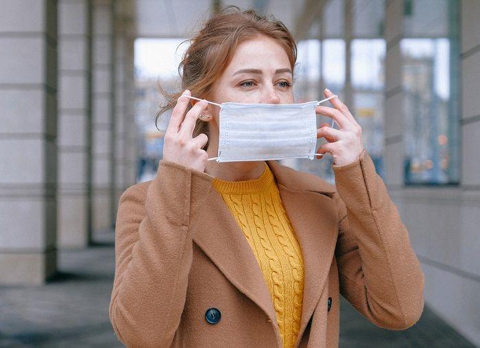 Frau steht in einer Stadt und legt gerade einen Mundschutz an