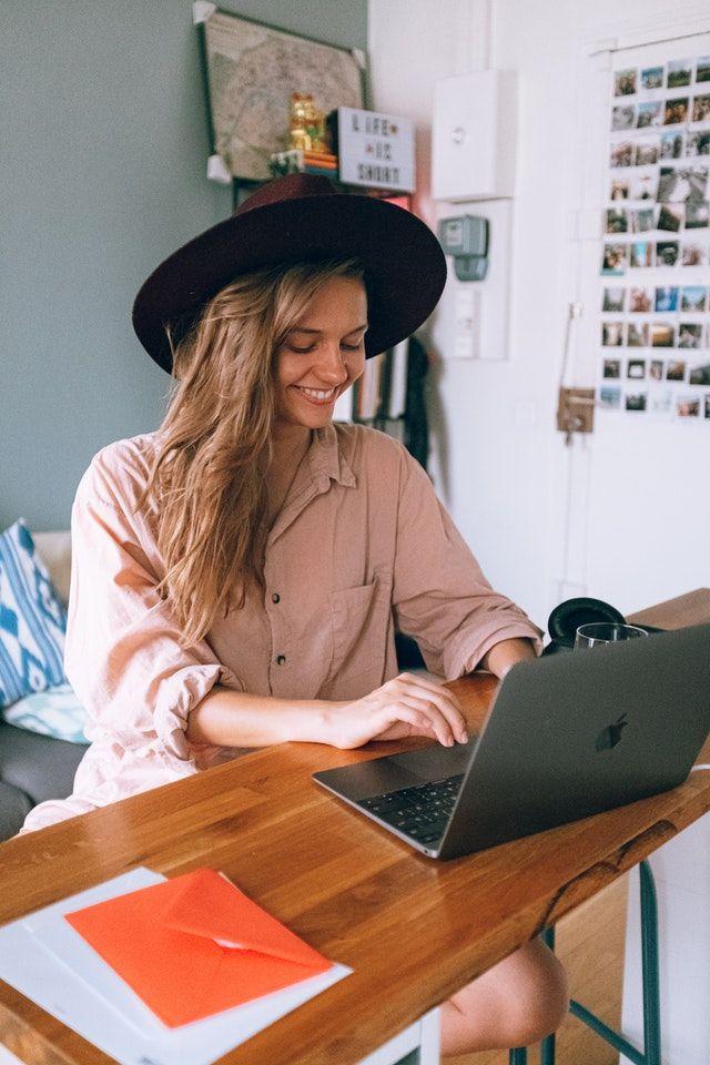 Frau sitzt alleine zuhaus, vergnügt vor Ihrem Laptop