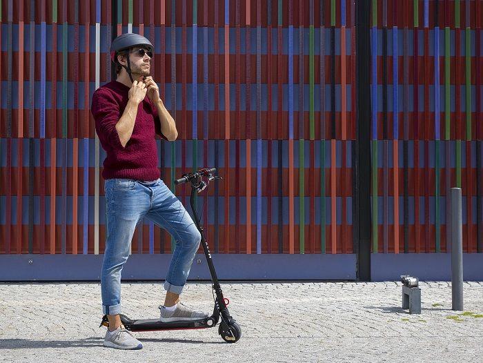 Junger Mann steht mit seinem E-Scooter auf einer Strasse