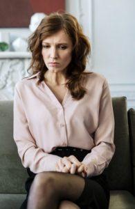 Frau sitzt zurückhaltend auf einem Sofa