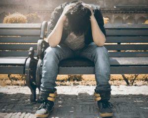 Junge sitzt mit Schmerzen und resigniert auf einer Parkbank