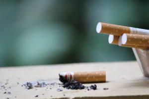 Eine offene Zigarettenpackung, daneben ein Zigarettenstummel und Asche