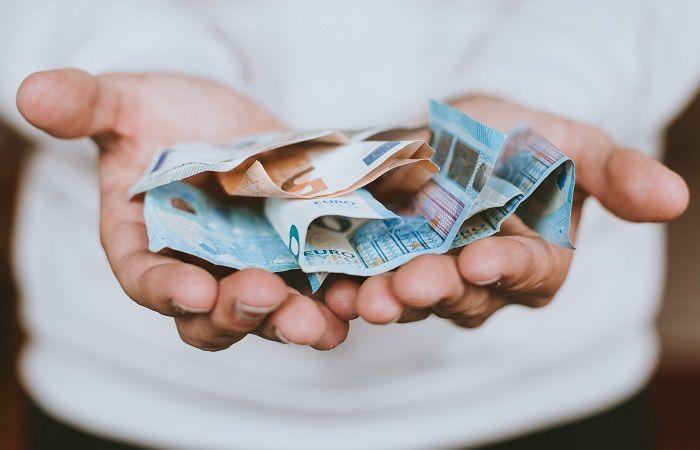 Männerhände halten mehrere Euro Geldscheine offen hin