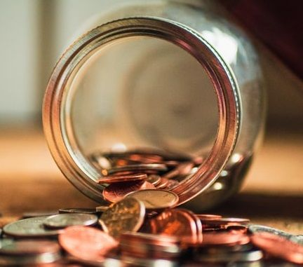 Sparglas liegt umgefallen auf einem Tisch und Münzen quellen heraus