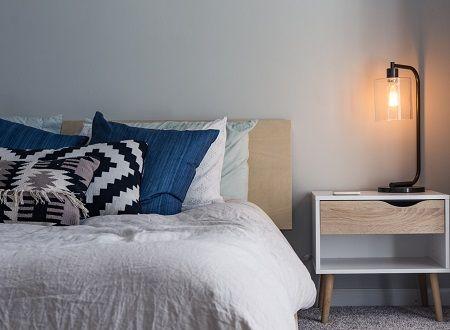 Bett mit vielen Kissen und einem Nachtkästchen