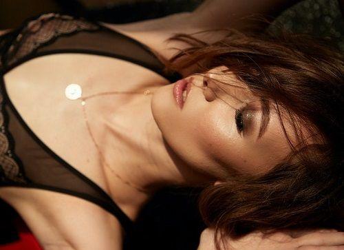 Frau liegt fast nackt am Rücken und genießt lustvoll