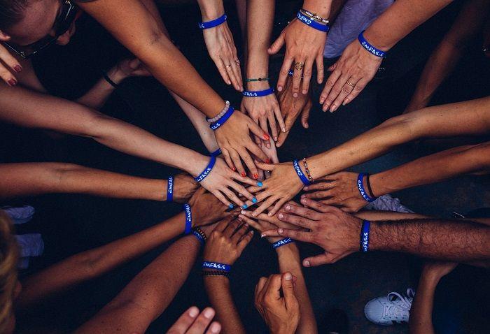 Verschiedene Menschen legen, zum Zeichen der Solidarität, die Hände übereinander