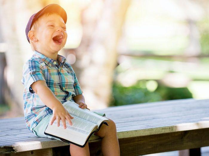 Junge sitzt mit einem Buch lachend auf einer Bank im Freien