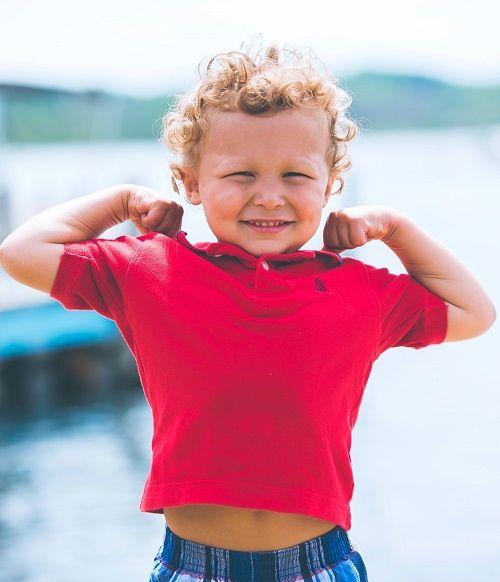 Junge hebt beide Arme und zeigt seine Muskeln