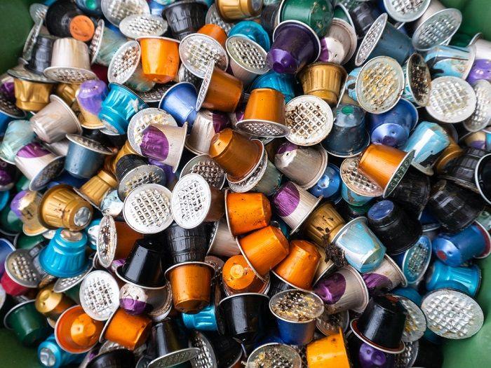 Viele Kaffekapseln in verschiedensten Farben liegen in einer Mülltonne
