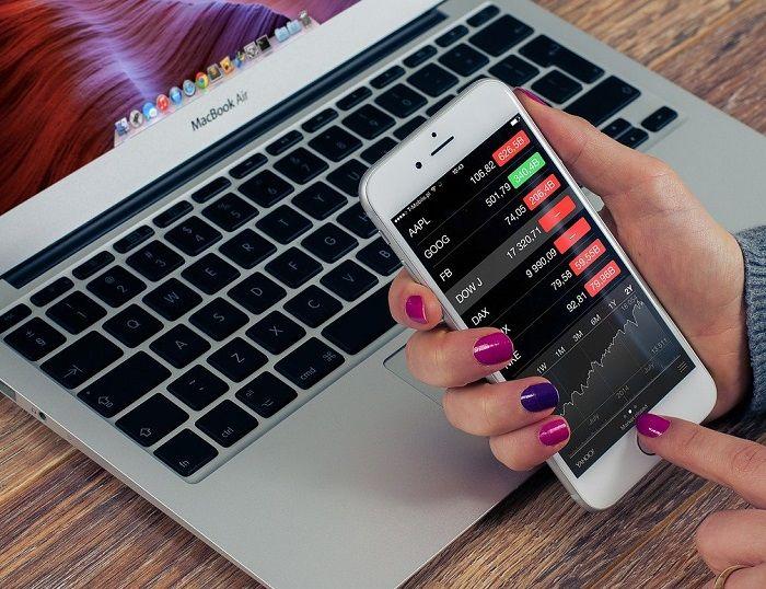 Frau sitzt mit dem Handy vor einem Laptop und prüft Aktienkurse