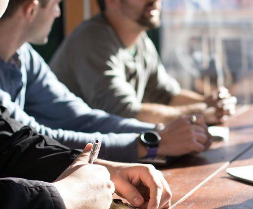 Männer sitzen, besprechend und mit Notizblöcken vor sich, an einem großen Besprechungstisch