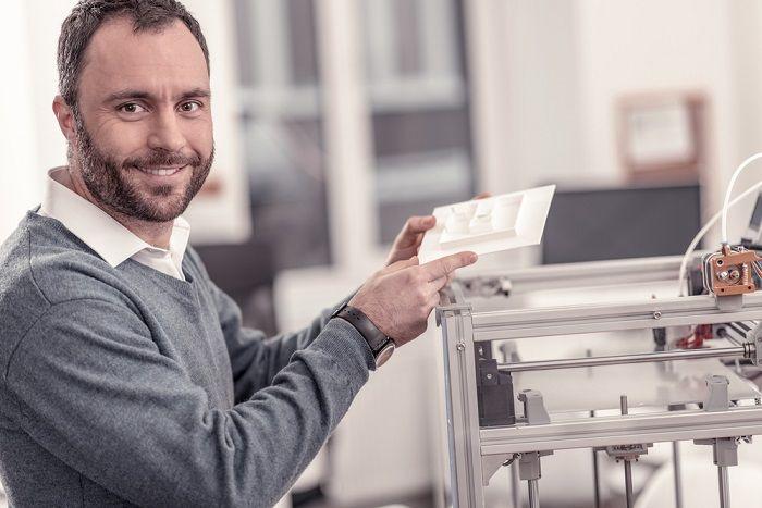 Mann zeigt an einem 3D Drucker ein ausgedrucktes Modell
