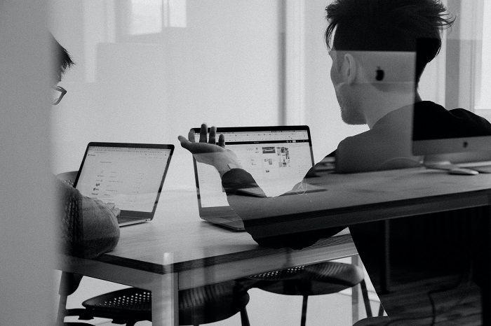 Junge Männer sitzen, mit Laptops vor sich, in einem Büro und recherchieren im Internet
