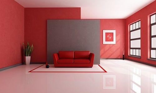 Ein großes Wohnzimmer mit rotem Sofa vor grauer Wand